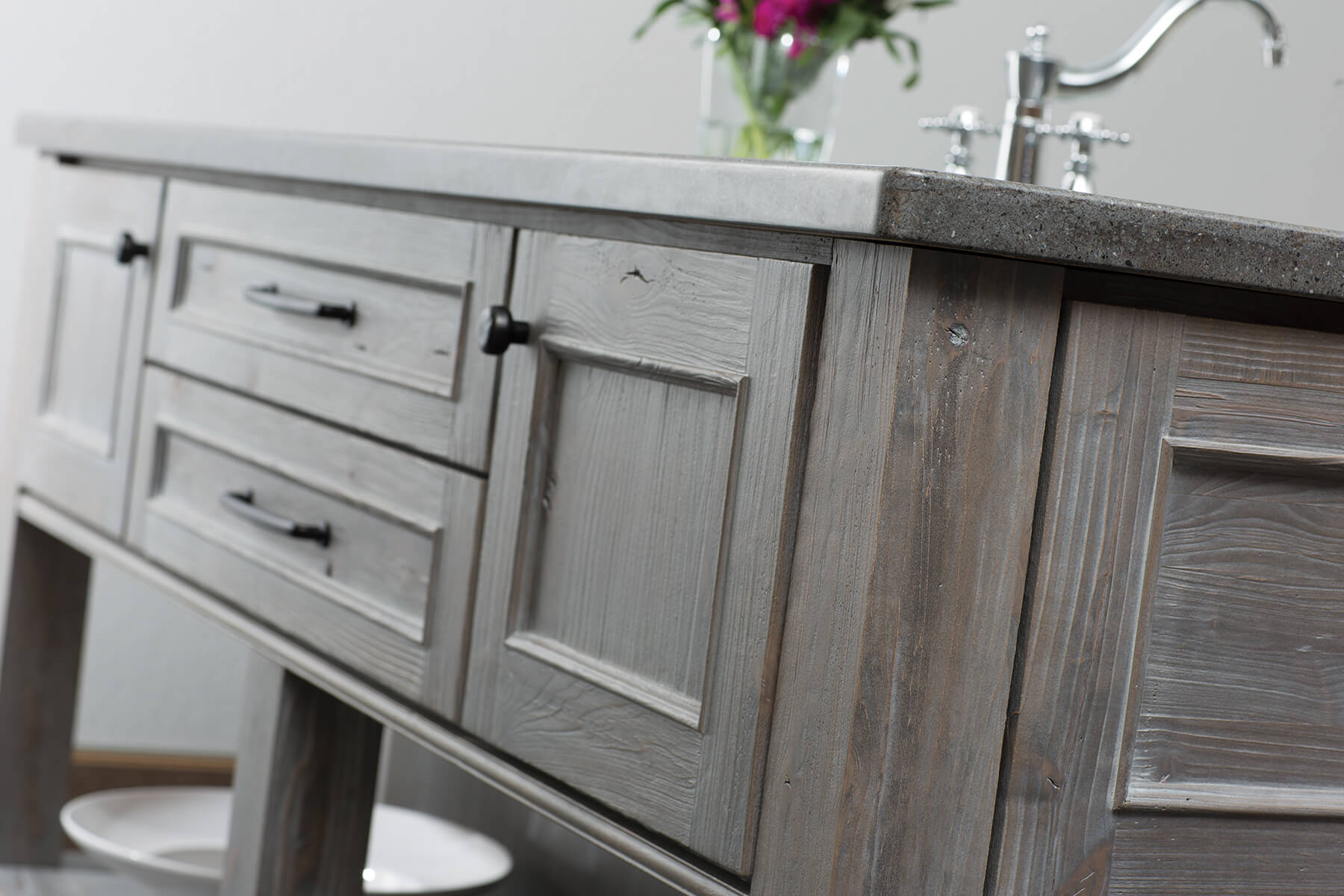 A gray stained kitchen island with weathered wood cabinets from Dura Supreme Cabinetry.