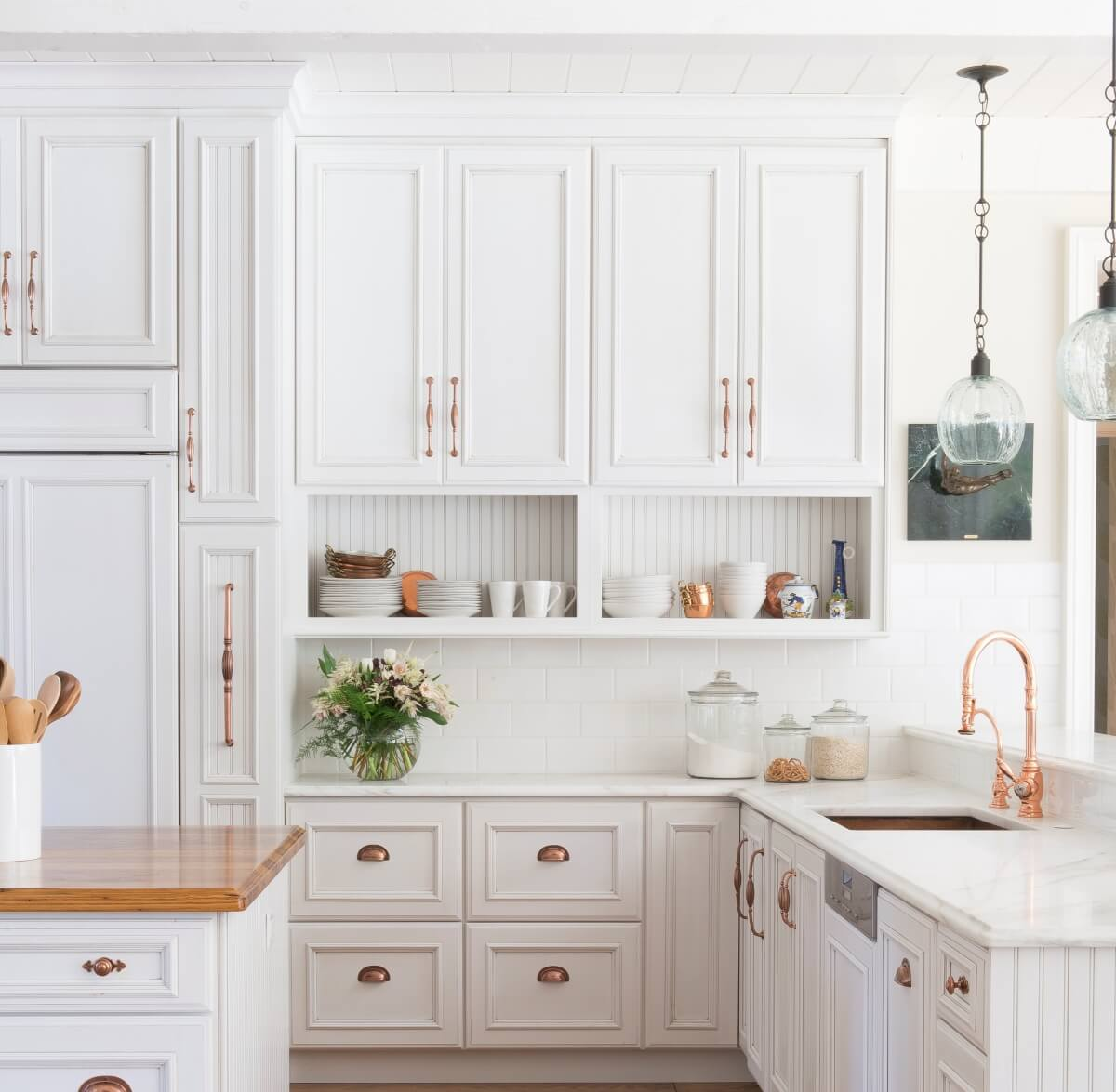 A French Farmhouse style kitchen remodel with bright white painted cabinets and copper hardware. A Dura Supreme kitchen featuring Wall Cabinets with Open Display Below.