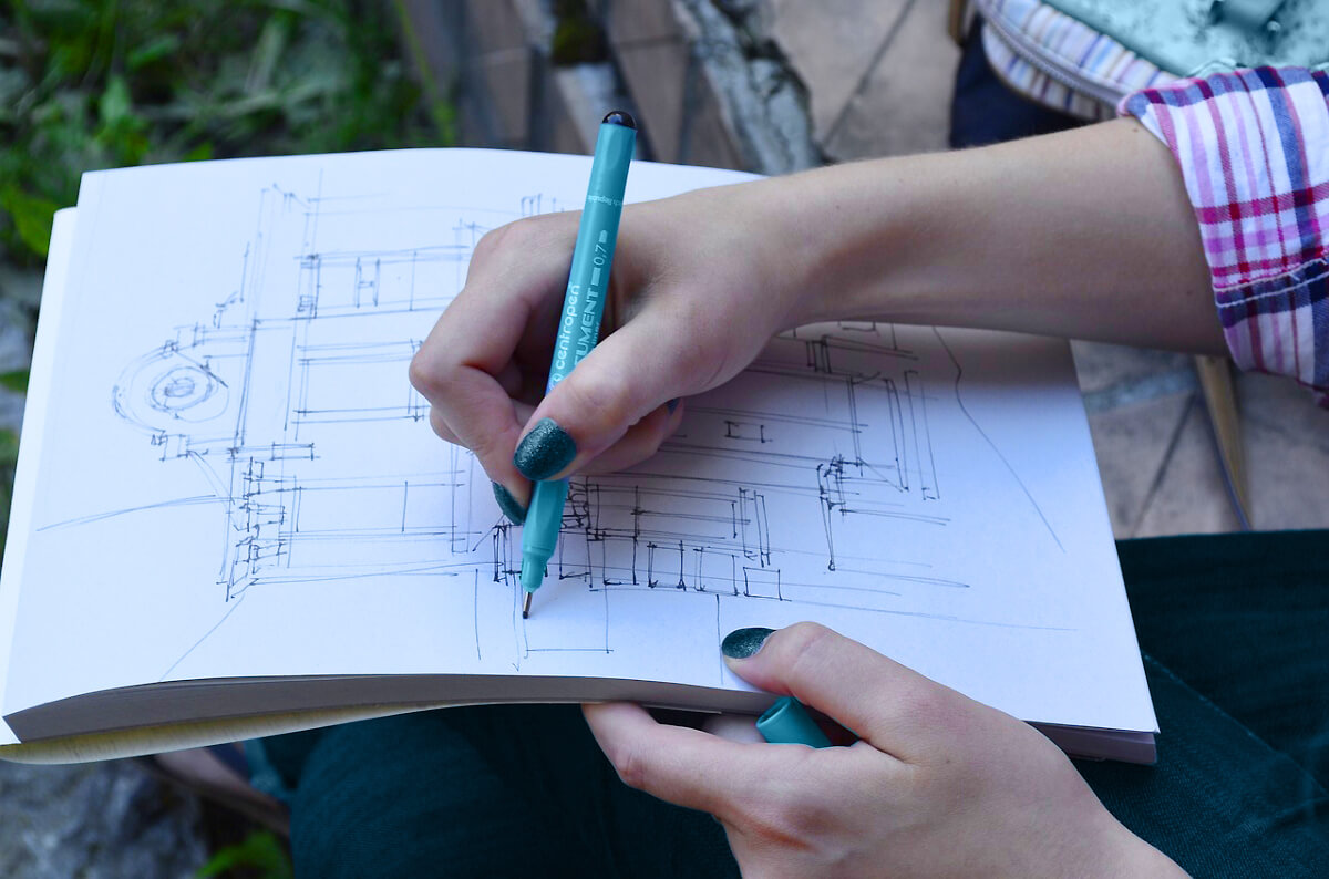 A close up of a kitchen designer drawing the cabinet design and kitchen remodel plans.