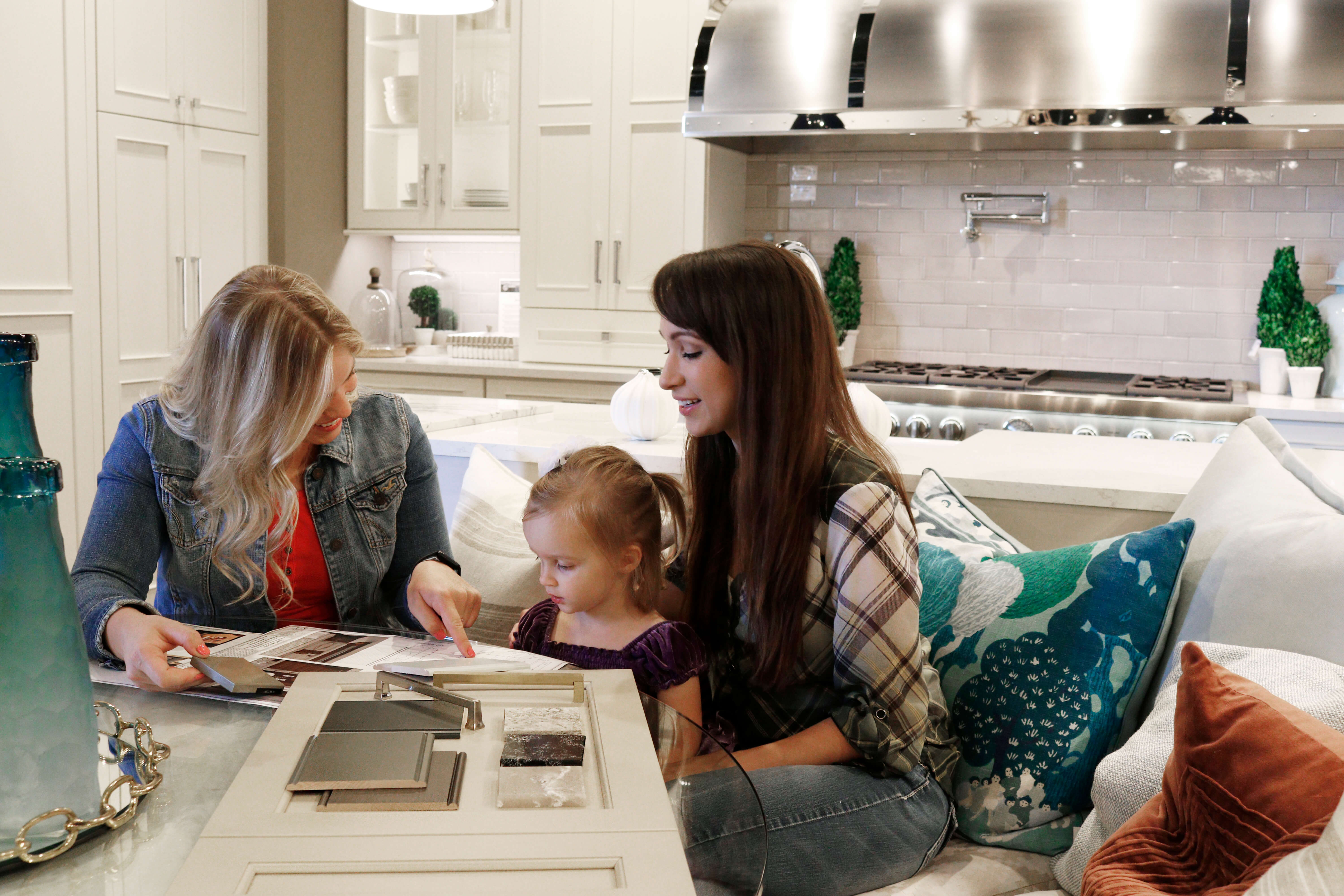 A mother and her child meeting with a Kitchen and Bath designer in a Dura Supreme Cabinetry Showroom.