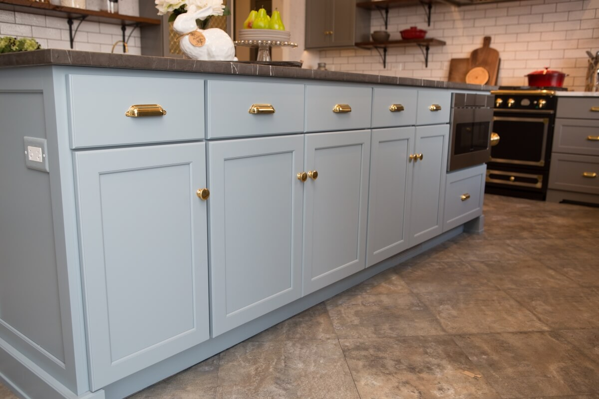 Kitchen island features Dura Supreme Cabinetry in the Kendall Panel door style in a blue custom color finish.