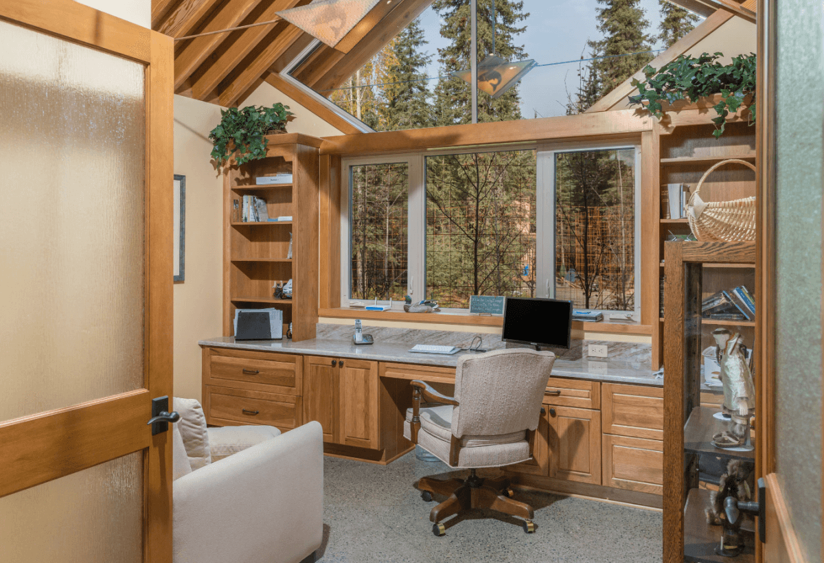 A lovely built-in home office resides in front of a window with a gorgeous view of the outdoors. The home office is designed by Hollie M. Ruocco, CMKBD of Creative Kitchen Designs, Inc featuring Dura Supreme Cabinetry in the Chelsea door with Hickory Butternut finish.