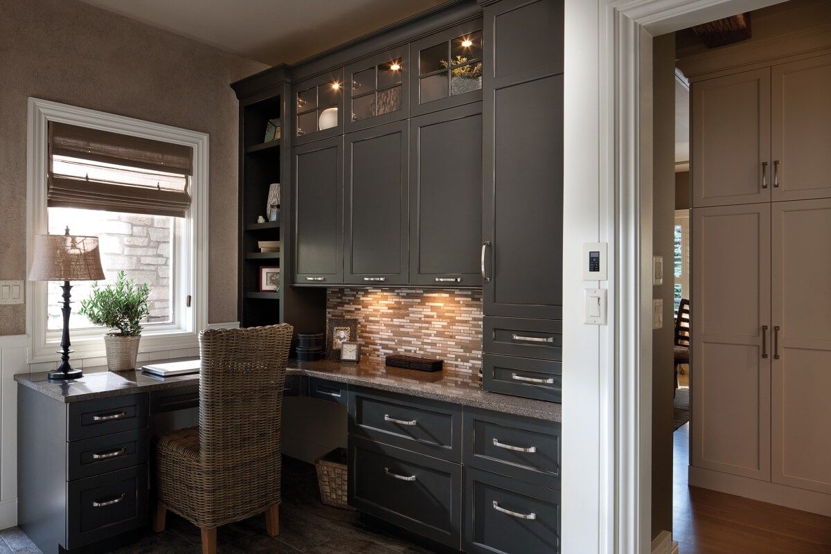 A stylish home office designed by Mingle, featuring Dura Supreme Cabinetry. Door style: Arcadia Panel in custom rubbed-thru finish.