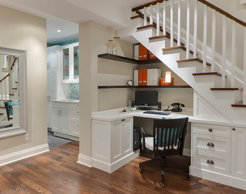 Photo by Leslie Goodwin Photography featuring an under the stairs office desk built-in.