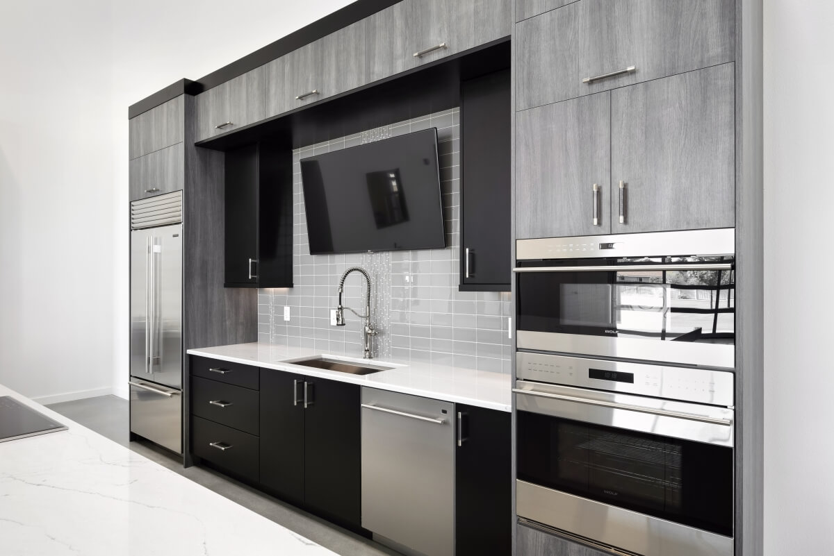 Simple, contemporary styled molding was selected with a Black paint finish to frame the wall and tall cabinet to make them appear as one unit.