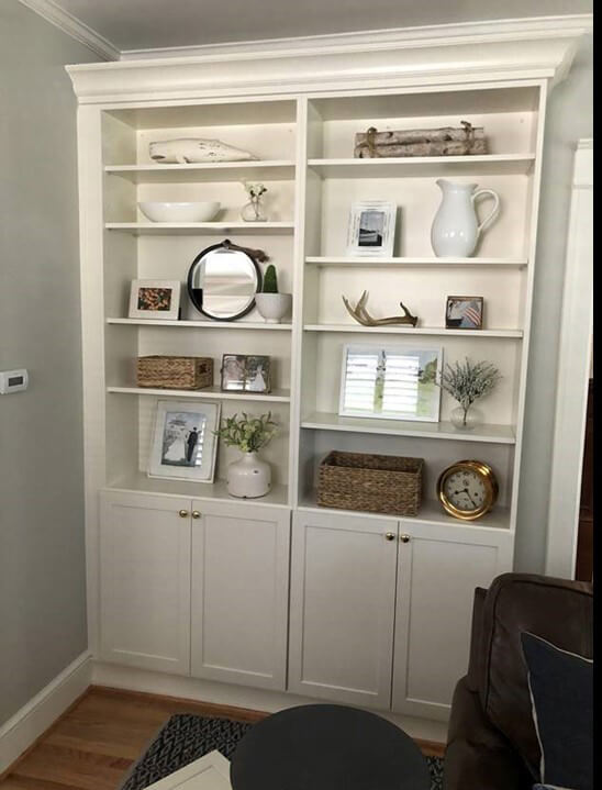 A Classic White Dura Supreme Cabinetry bookshelf creates a lovely transition from the kitchen into the living room.