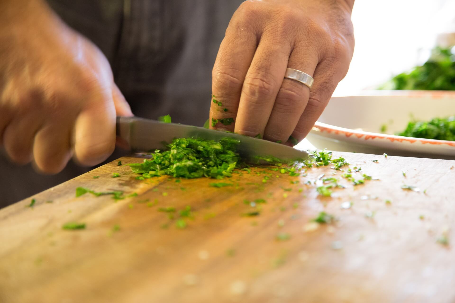 man in kitchen chopping and preparing food.