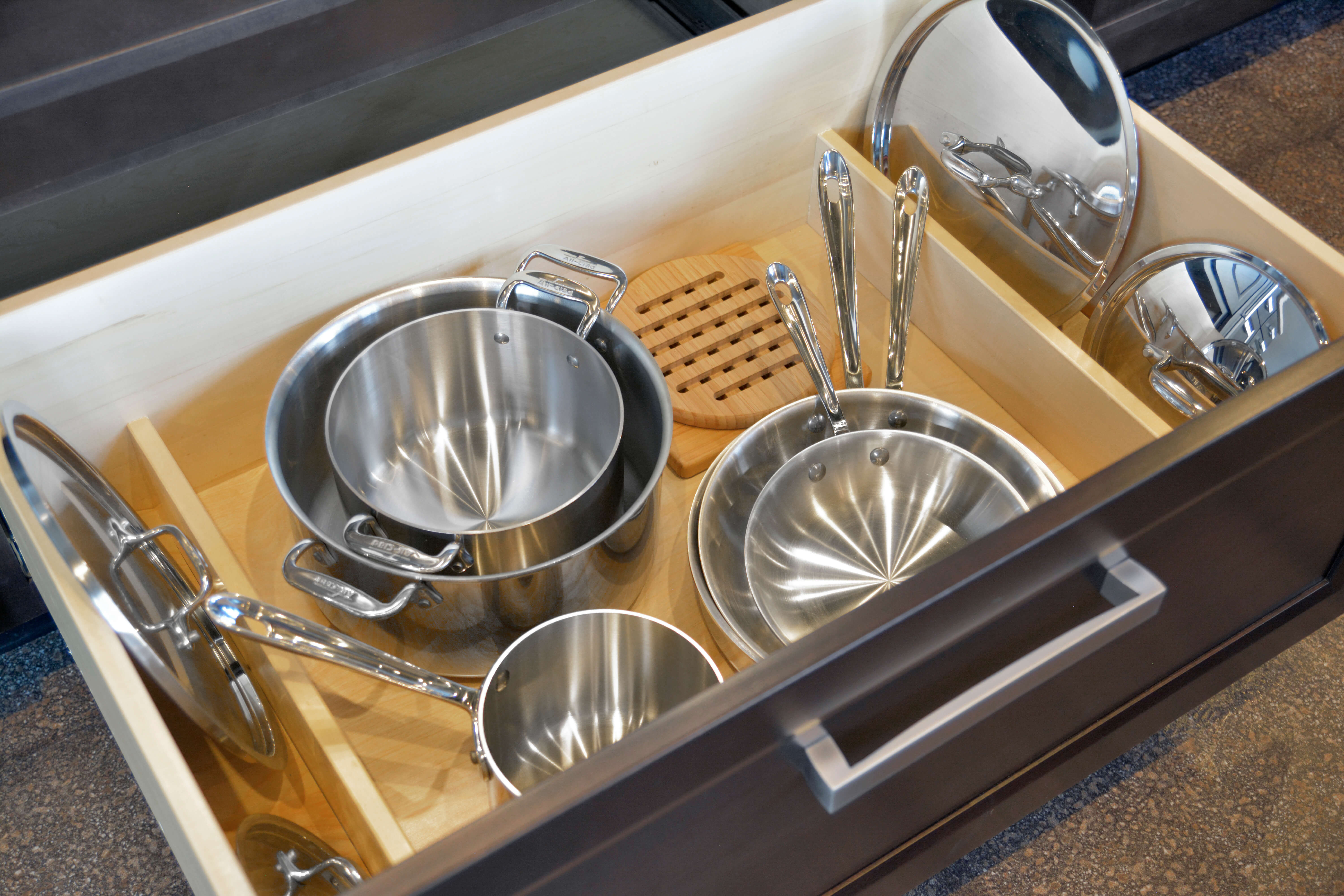 A deep drawer below a cooktop is an ideal location for pots and pans. Add Dura Supreme's Lid Storage Partitions (LSP-S) to stand lids on both sides of the drawer for easier access.