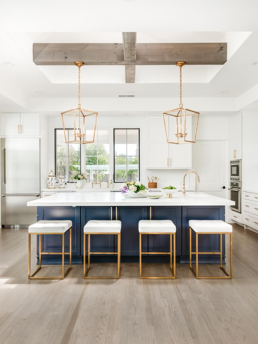 This kitchen island dramatically contrasts the white cabinetry and includes a clean-up center. Dura Supreme Cabinetry design by Helena Steele of Golden Gate Kitchens. Photo by Christopher Stark Photography.