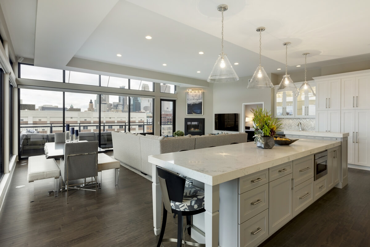 This kitchen island helps divide the kitchen space from the living space. Dura Supreme Cabinetry design by Ispiri Design Build Remodel.