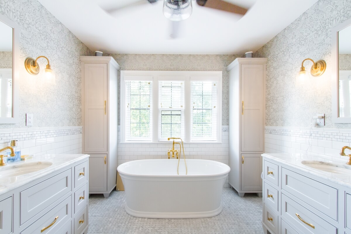 A bright white bathroom with light gray painted vanities for two, a free-standing bathtub with a view and brassy gold cabinet hardware.