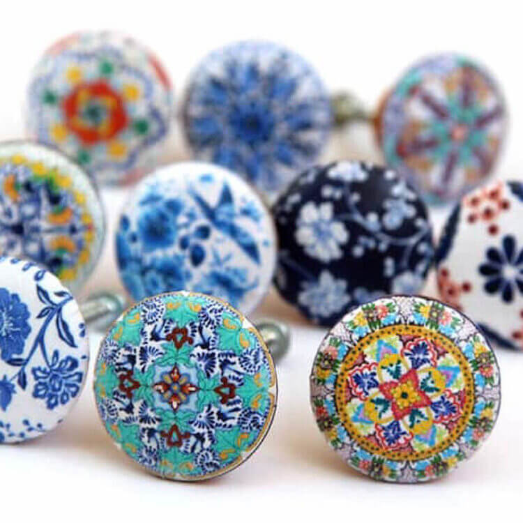 a close up of unique eclectic styled hardware for kitchen and bath cabinets with hand-painted designs.
