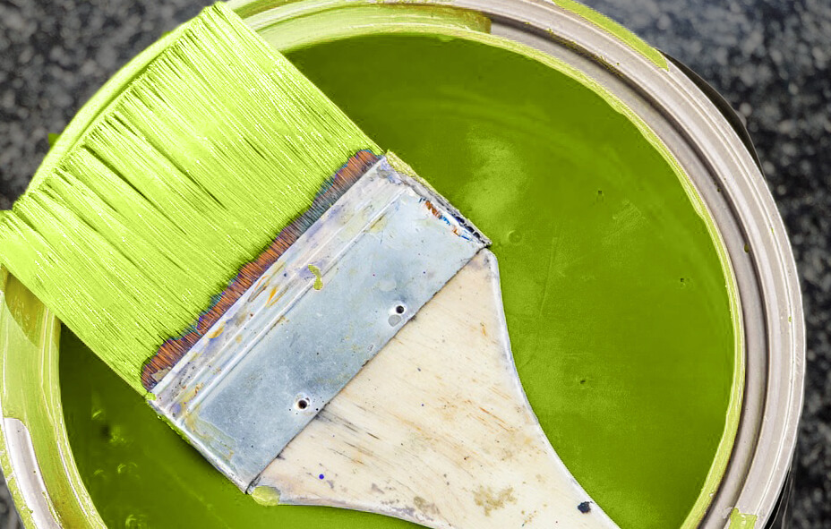 Selecing a custom paint color for kitchen cabinets. Bright green paint can and paint brush.