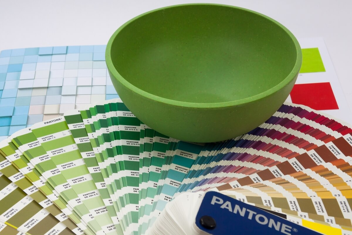A kitchen designers desk with interior design tools including a pantone color book with paint color samples and ideas.
