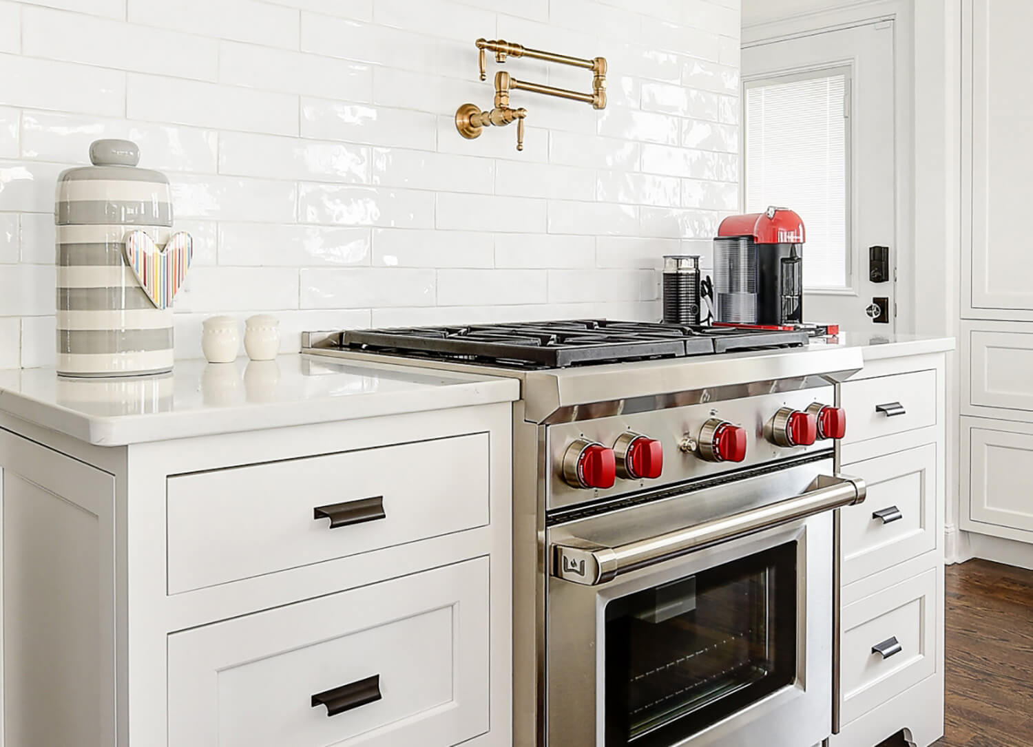 A beautifull all white kitchen with dark hardwood floors, white pianted inset cabinets, and crisp white countertops.