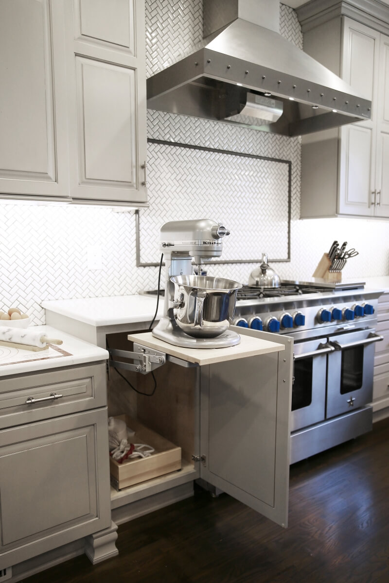 Their well used KitchenAid mixer has a happy home in an appliance lift cabinet next door to the baking center's prep space.