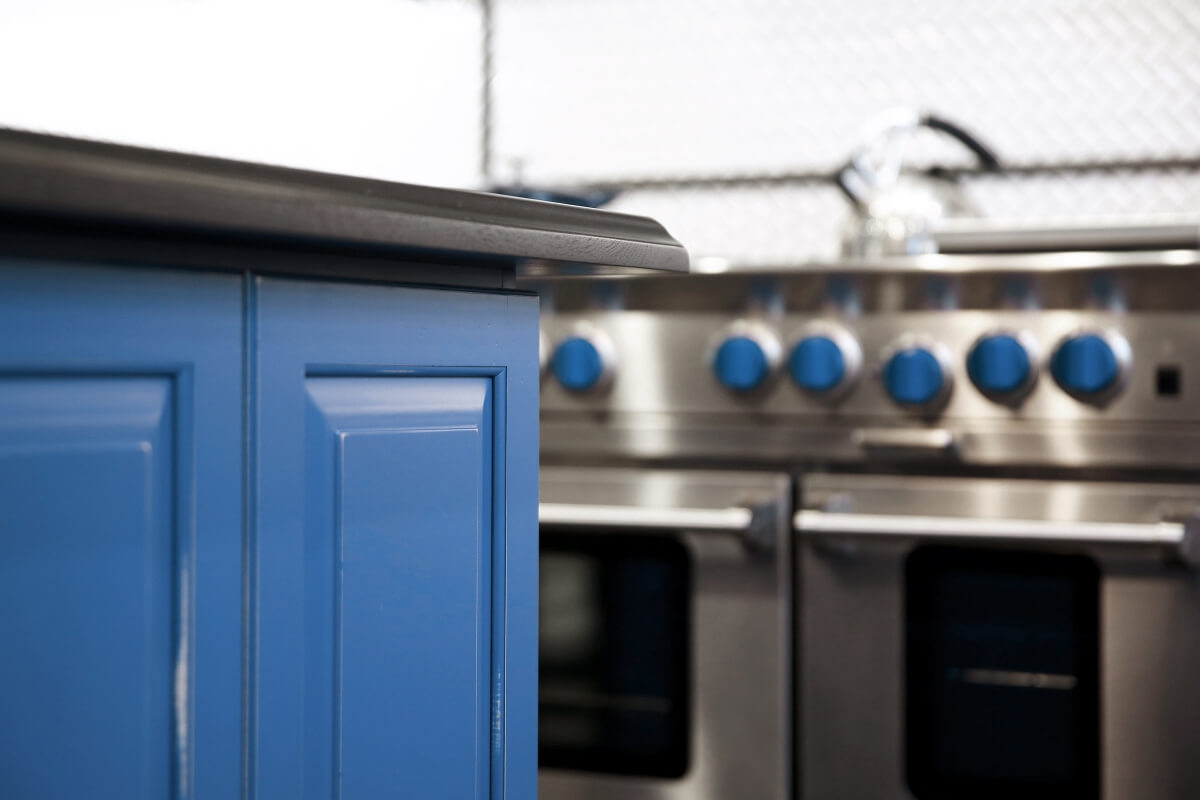 The kitchen island shown in a custom blue artisan finish by Dura Supreme Cabinetry.