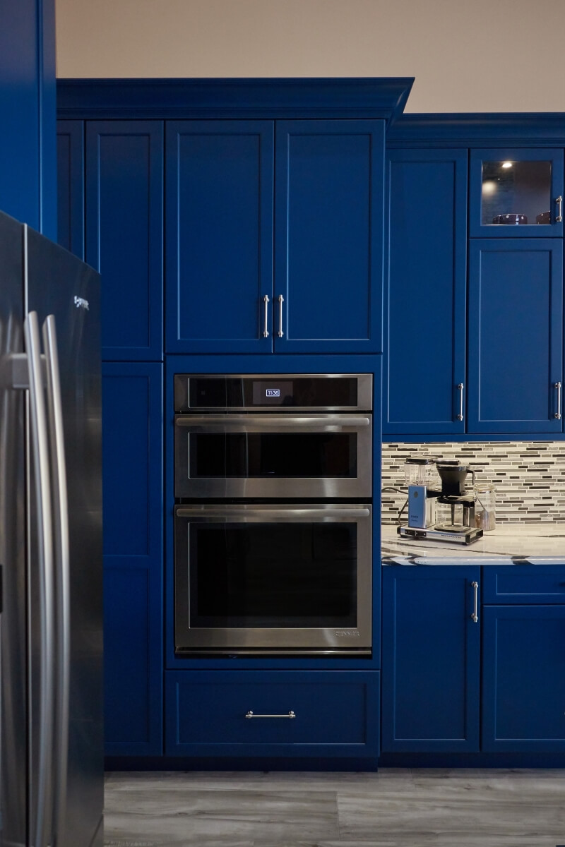 The Sherwin Williams Loyal Blue paint finish sets the stage for these flush inset oven appliances.