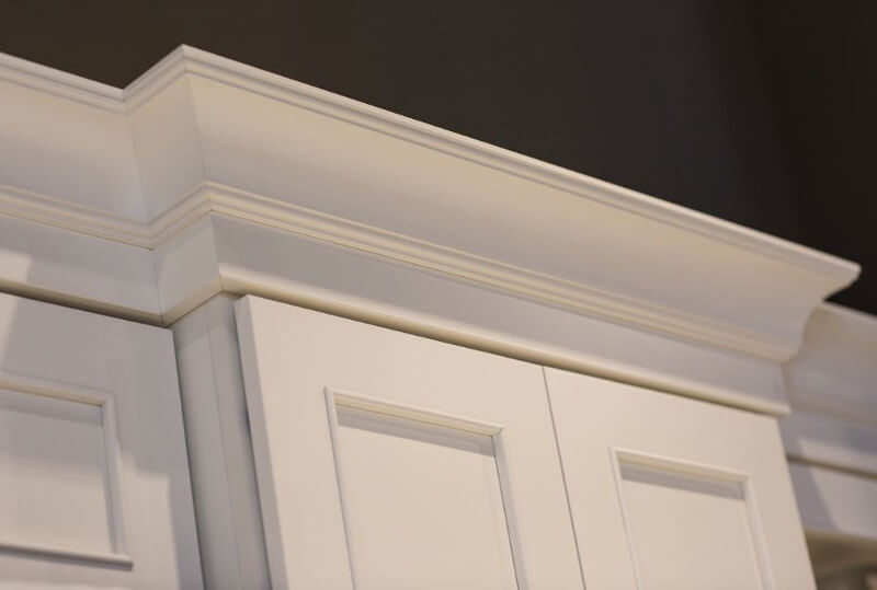 Crown molding on the top of white painted kitchen cabinets from Dura Supreme Cabinetry.