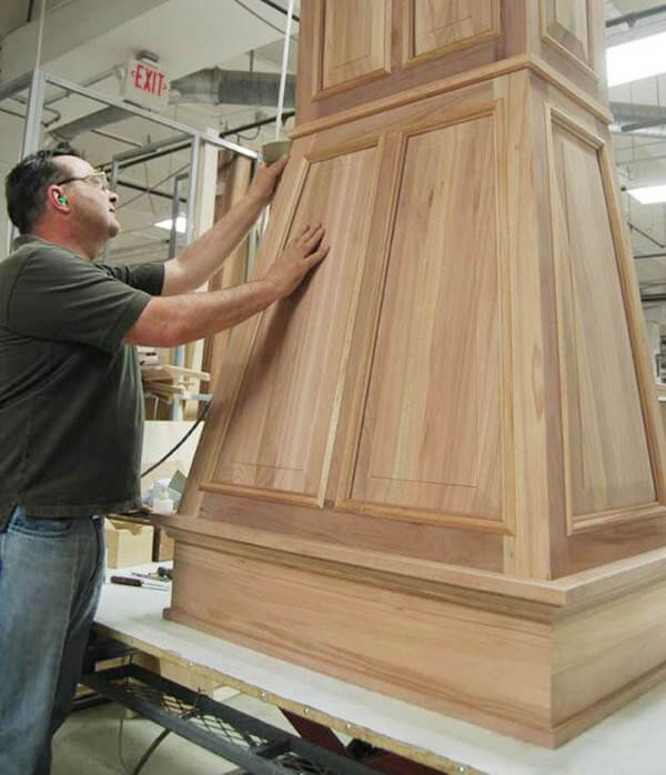 One of our Master Builders doing a final sanding on this custom-designed wood hood prior to finishing.