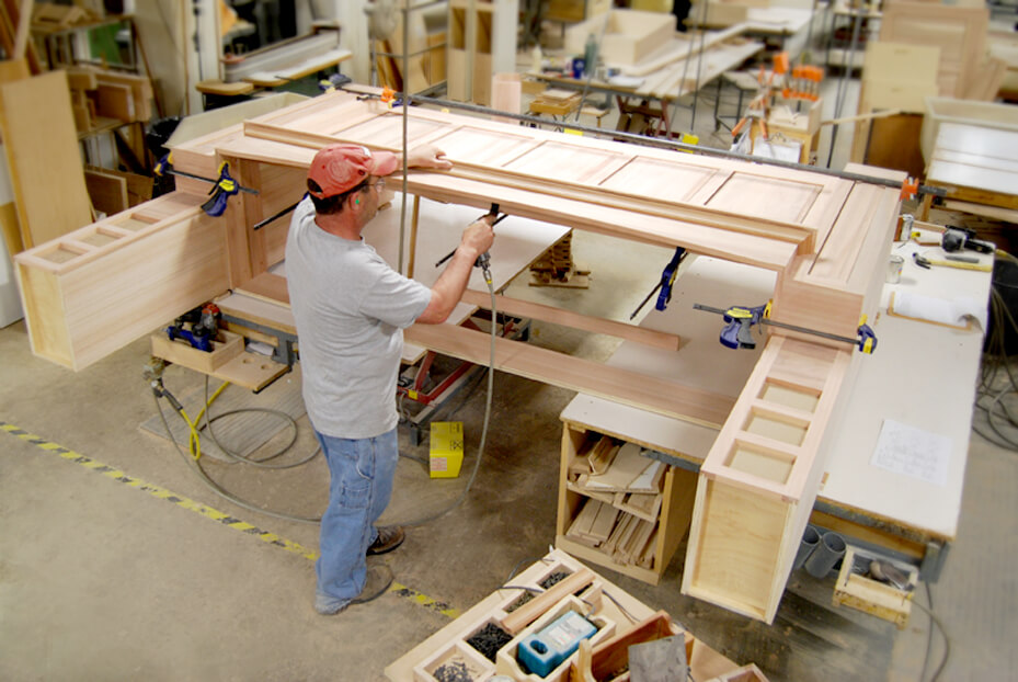 One of our Master Craftsman constructing a Dura Supreme Wood Hood. Dura Supreme Master Builder working on the molding details of a large wood hood.