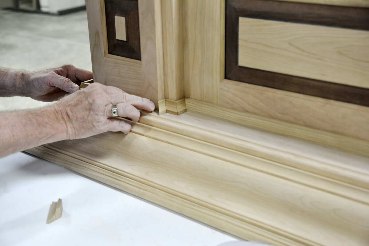 Dura Supreme Master Builder working on the molding details of a large wood hood.