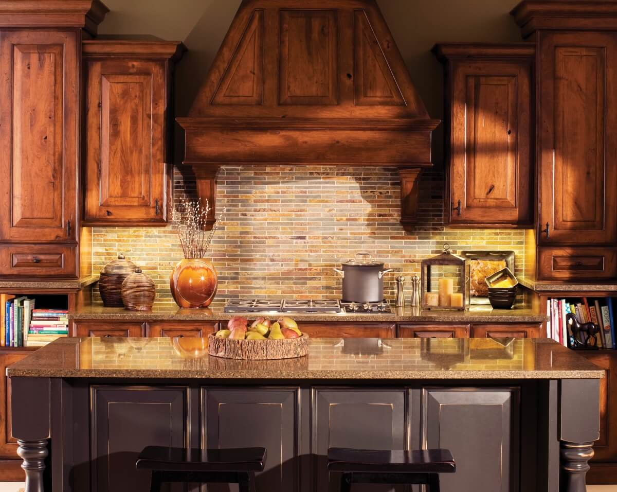 The backsplash tile features a rough-hewn, stone texture and earthy coloring.