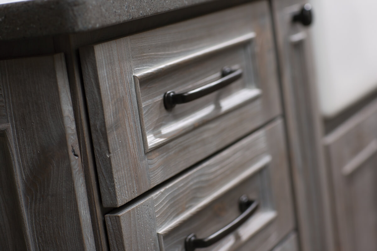A close up of weathered wood cabinets that look like drifwood and aged barnplanks. Cabinetry from Dura Supreme Cabinetry.