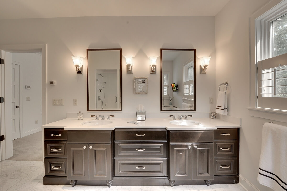 This bathroom design by Kristen Peck of Knight Construction Design, Inc. in Chanhassen, MN features the ideal distance between two lavatory sinks. The center drawer bank not only provides storage but extra space between the two lavatories.