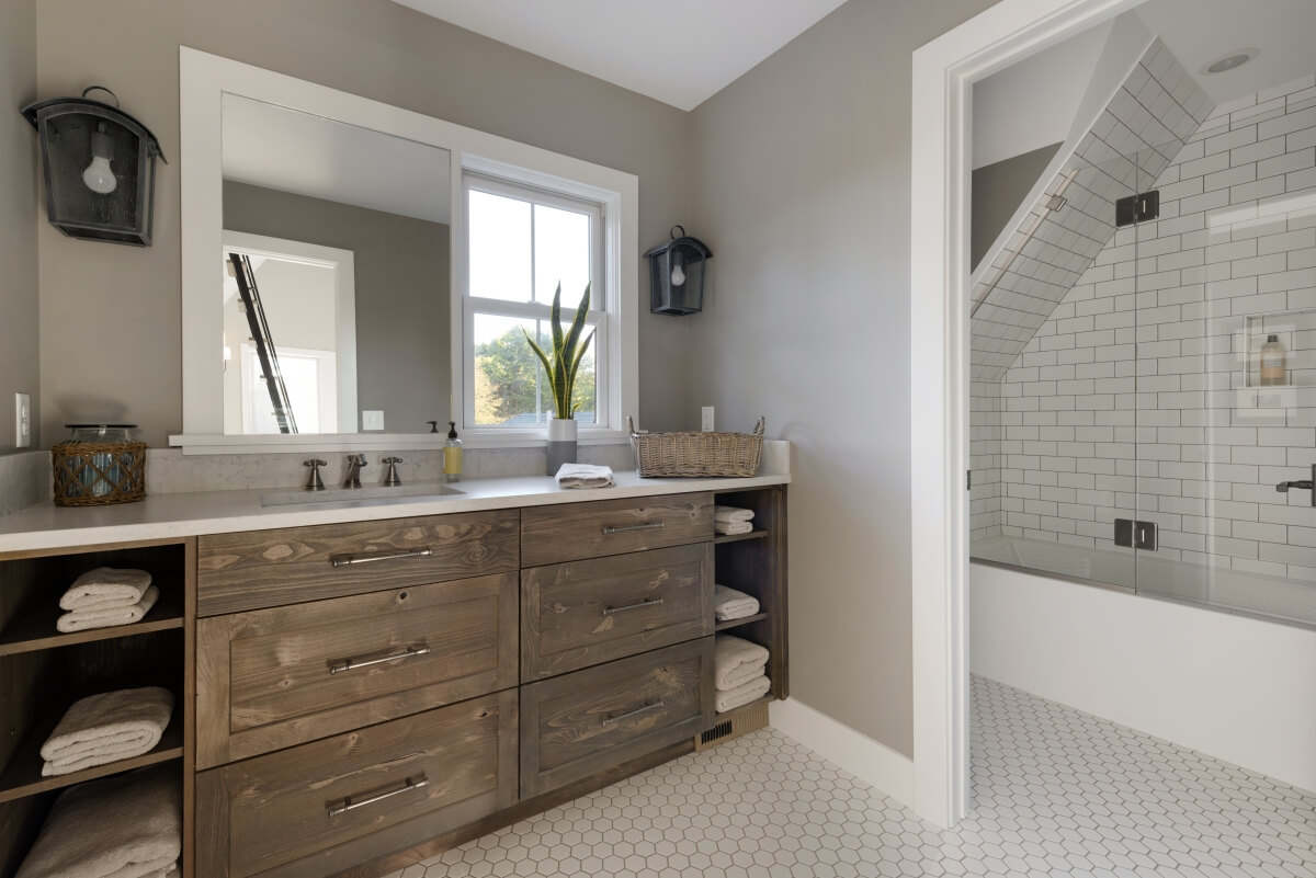 This charming bathroom is a great example of a single lavatory vanity that follows the suggested NKBA Lavatory Placement Guideline. Designed by Studio M Kitchen & Bath, Plymouth, MN and photographed by Spacefrafting Photography.