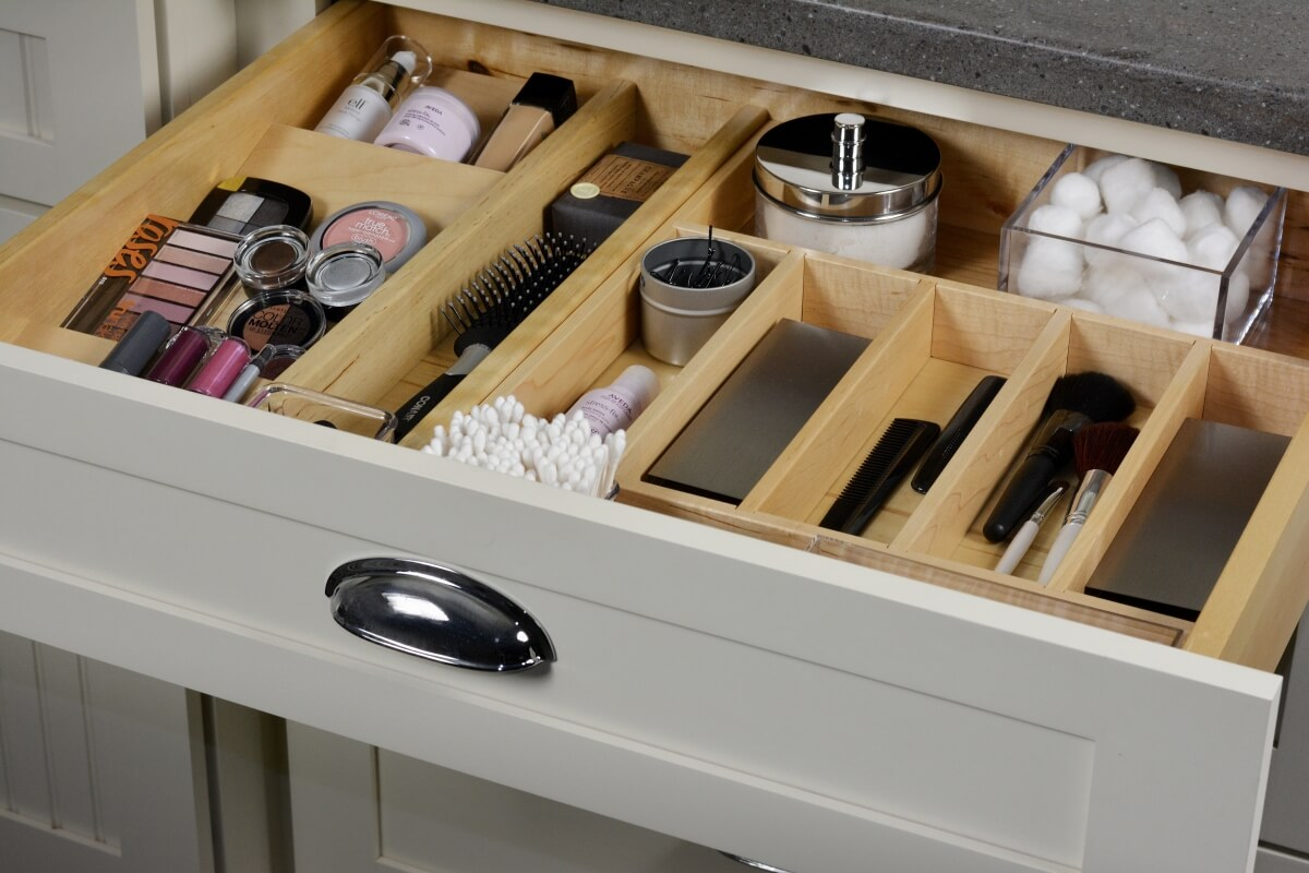 Wide drawer with organized divered for bathroom storage. Bathroom cabinets by Dura Supreme Cabinetry.
