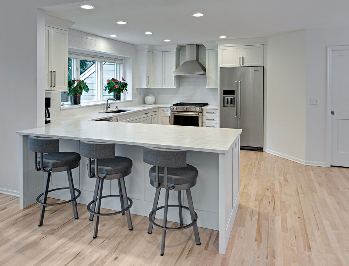 A stunning example of a U-Shaped kitchen design utilizing an open concept floor plan by incorporating a pennisula into one of the legs of the
