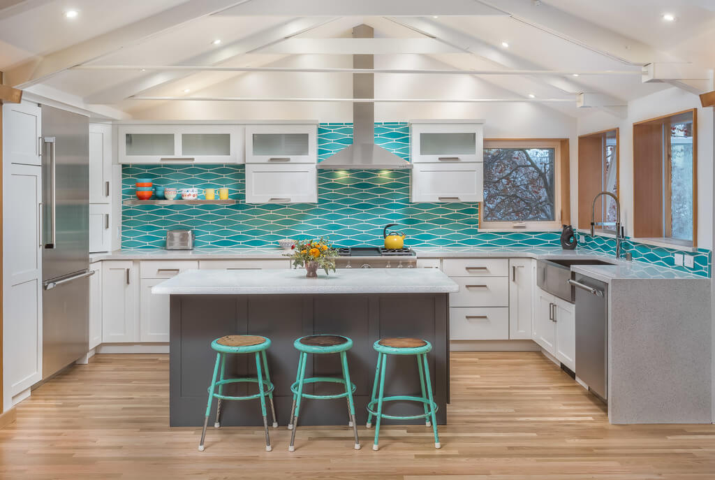 A fun and colorful U-shaped kitchen with white painted cabinets from Dura Supreme and aqua blue tiled backplash.