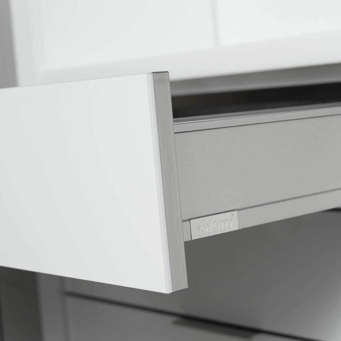 A close up of a stainless steel drawer with contemporary kitchen cabinets with an acrylic finish.