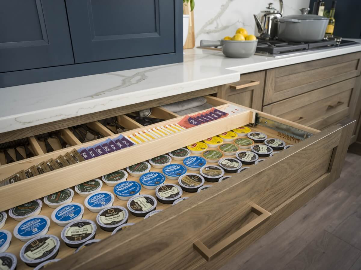Two-Tiered Storage for K-cups, tea bags and drink supplies below Beverage Center from Dura Supreme Cabinetry