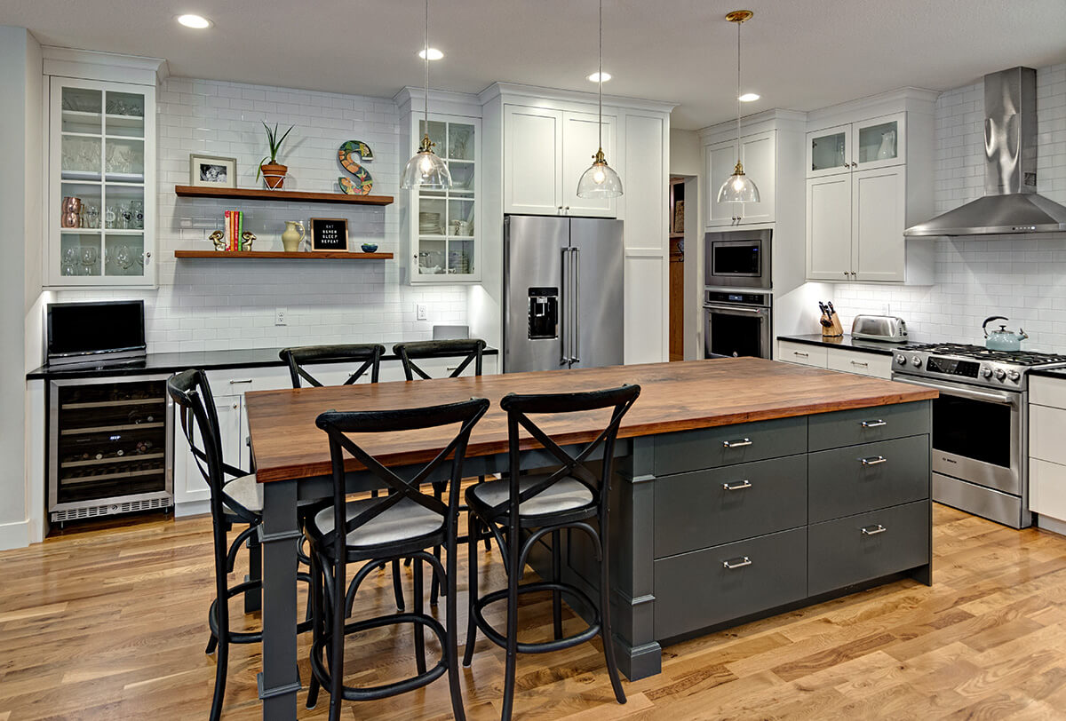 A white and gray painted kitchen with dark gray kitchen island and medium wood foors.