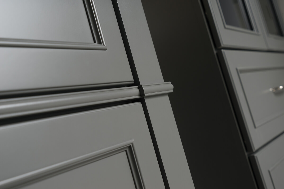 A close up of bathroom vanity cabinets and cabinet doors with a dark gray painted finish..