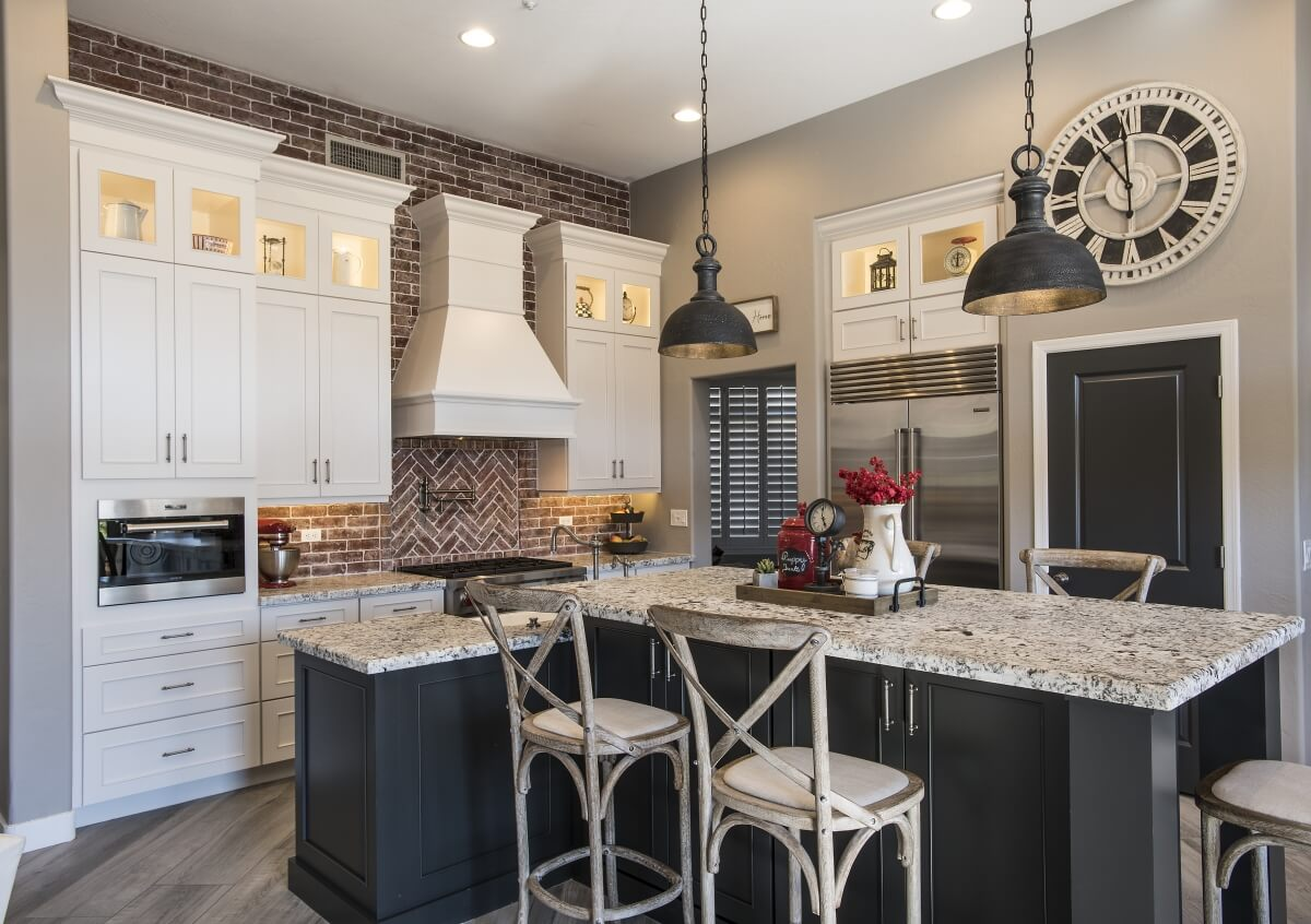 A traditional styled farmhouse kitchen remodel featuring a natural brick backsplash, a painted wood hood and a dark gray (almost black) kitchen island.