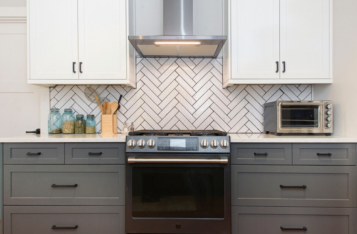 A new kitchen remodel with white painted upper cabinets (wall cabinets) and dark gray painted lower cabinets (base cabinets) with a dynamic white with dark gray grouted herringbone backsplash and modern stainless steel appliances.
