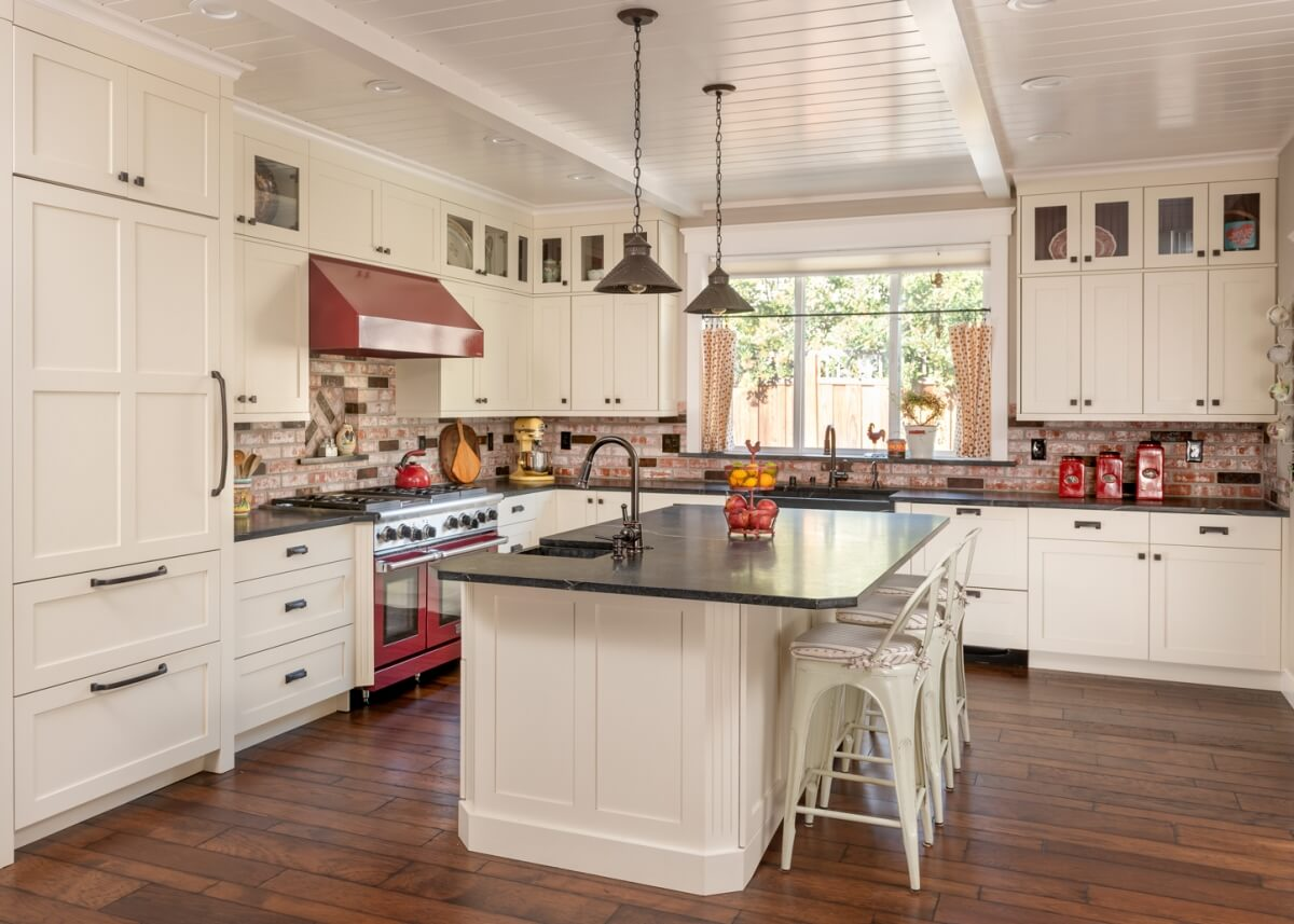 A modern farmhouse kitchen design with white painted cabinets, red brick backsplash, red accents, wood floors and contrasting dark black granite countertops.
