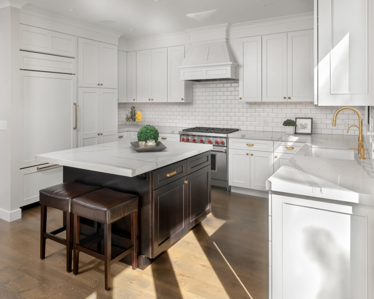 A new kitchen remodel with white painted cabinets, a black kitchen island, gold hardware, and coordinated white quartz countertops that match the cabinetry colors well.