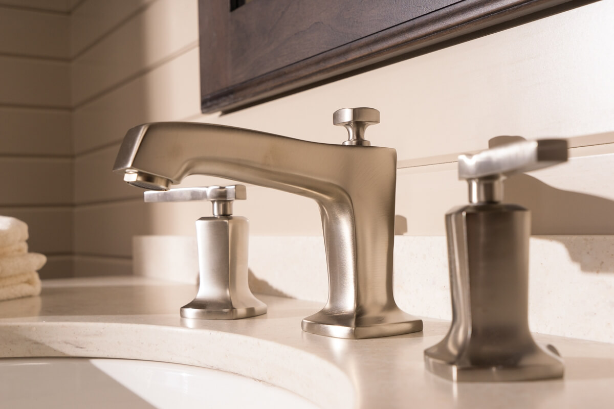 A close up of a bathroom sink and faucet with Dura Supreme bathroom cabinets.