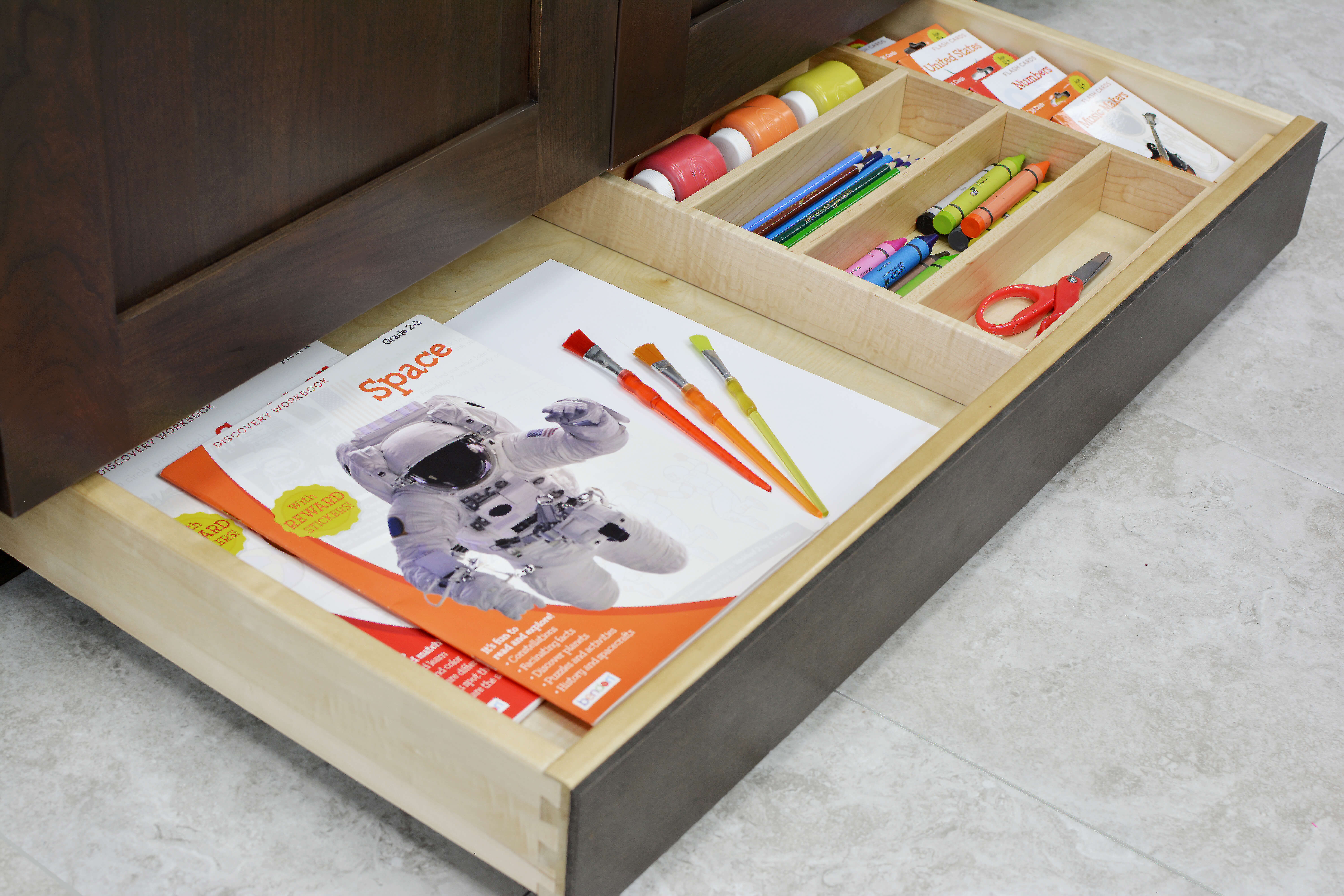 Miscellaneous items can find a home in a Dura Supreme Toe-Kick Drawer hidden at the foot of your cabinets. Add a Cutlery Divider for the extra organization to create a dedicated place for storing arts, crafts, and homework supplies. Place this solution near the dining room, a kitchen peninsula, or kitchen island where your household often sits to create a workstation that's easy to access and clean up.