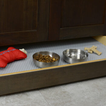 Miscellaneous items can find a home in a Dura Supreme Toe-Kick Drawer hidden at the foot of your cabinets. By adding a Dura Supreme Sink Mat you can create a treat station with toys, bones, and treats for your furry friend. Please note, this is a shallow drawer and can not fit standard depth feeding dishes.