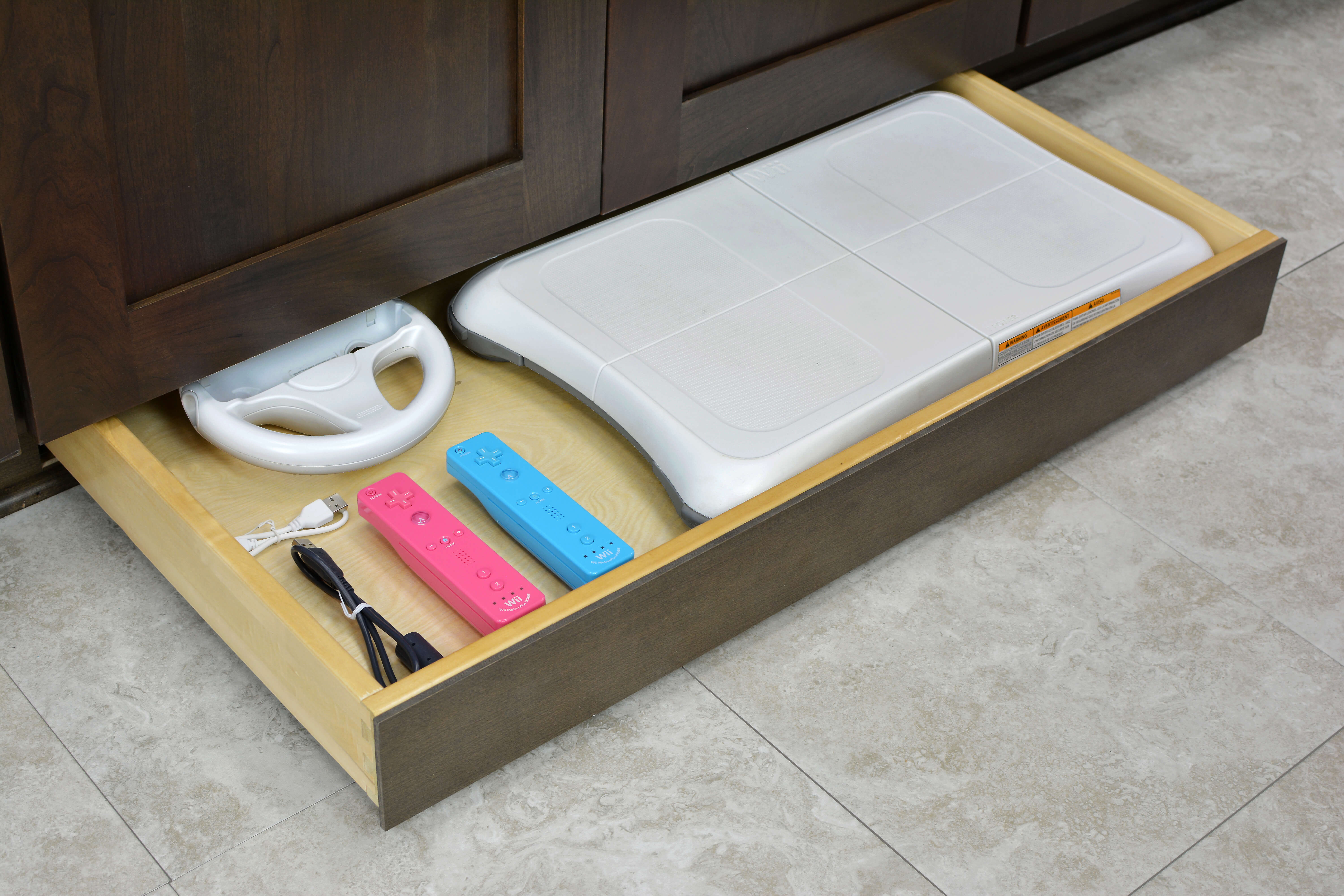 Miscellaneous items can find a home in a Dura Supreme Toe-Kick Drawer hidden at the foot of your entertainment center cabinets. This handy solution can give your gaming controllers and accessories a home, helping your living space clutter-free and your equipment easy to access.