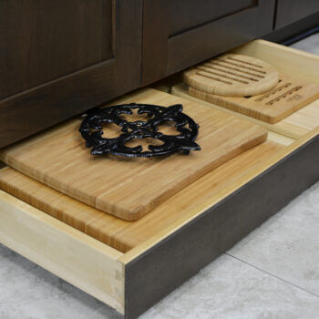 Miscellaneous items can find a home in a Dura Supreme Toe-Kick Drawer hidden at the foot of your cabinets. This convenient solution adds additional storage to your home. It's great for storing your cutting boards, trivets, rolling pins, and much more!