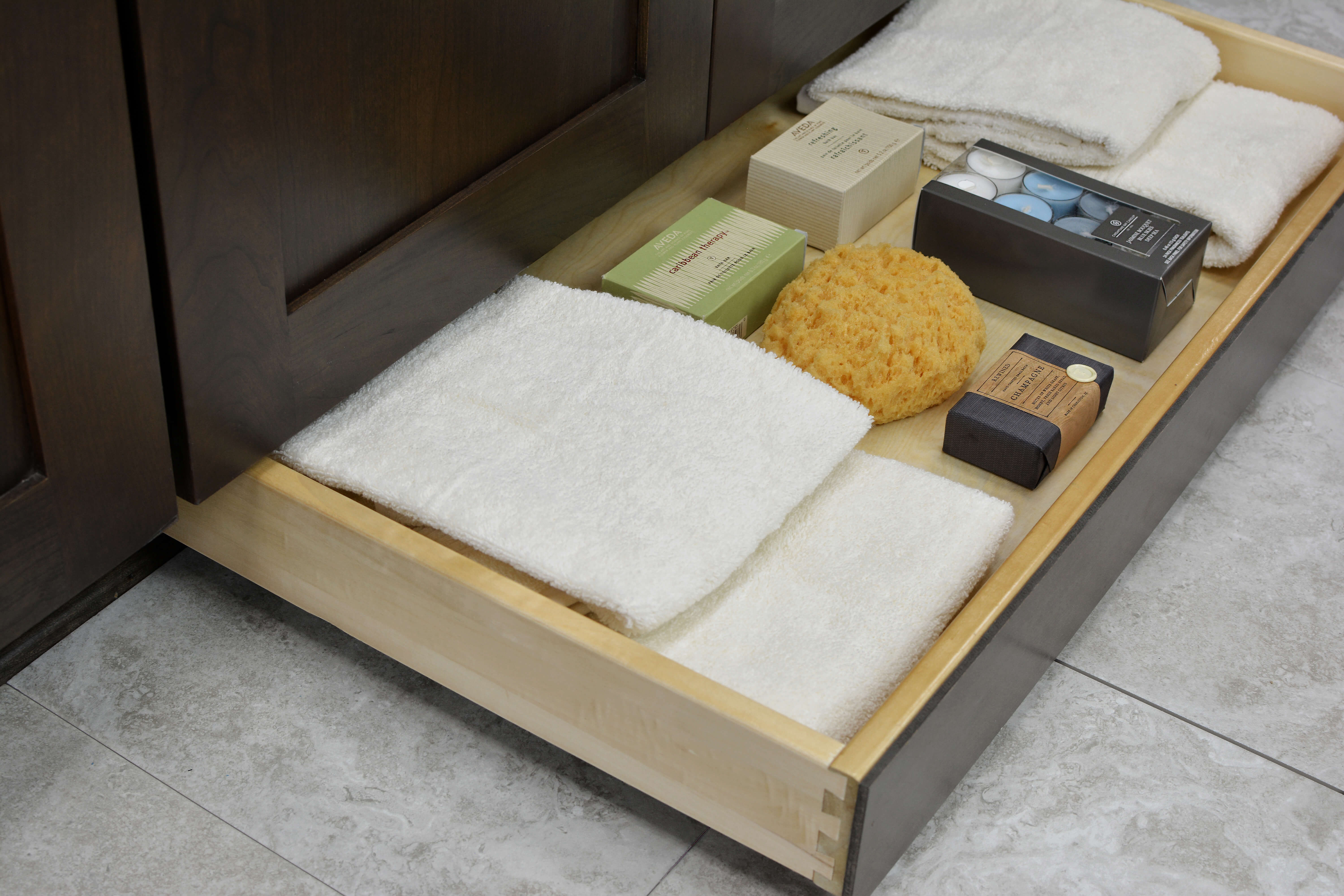Miscellaneous items can find a home in a Dura Supreme Toe-Kick drawer hidden at the foot of your cabinets. It is the perfect place for stashing your spare bathroom supplies to they're out of the way, yet close at hand when you need to restock.