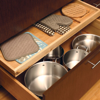 Conveniently store oven mitts and potholders in a Dura Supreme shallow roll-out above a pot and pant drawer (ROSAD).
