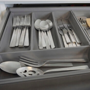 Modern kitchen cabinet drawer storage. Stainless Steel Cutlery Divider Tray from Dura Supreme Cabinetry.