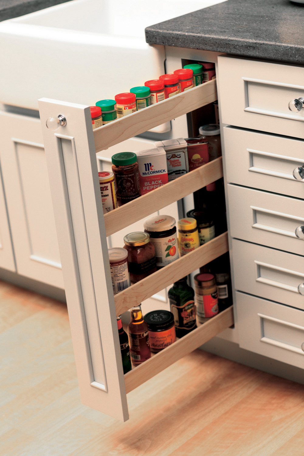 Small spaces offer a surprising amount of spice storage with a vertical Pull-Out Spice Rack. Kitchen Storage idea for spices and small pantry items from Dura Supreme Cabinetry.